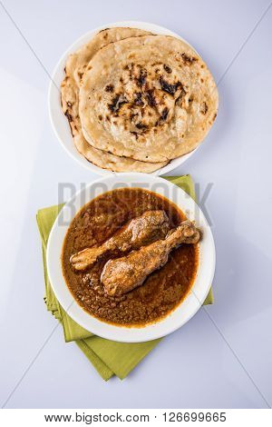 The most popular reddish chicken curry in the UK, india, pakistan, asia, chicken tikka masala, here served in bowl, accompanied by pilau rice and chapatis