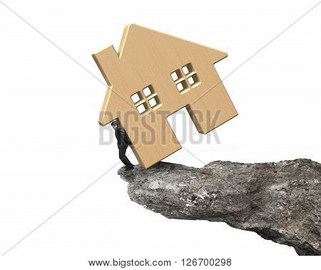 Man Holding Wooden House On Cliff Edge