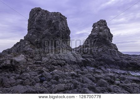 Two huge rocks tower above the sea at low tide on rocky coastline of Rosarito Baja California Mexico under moody cloudy grey sky