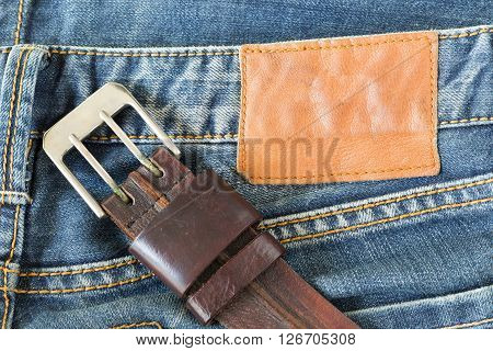 blue jeans with leather belt metal buckle and label tag