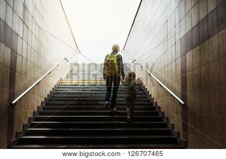mother and son walks up stairs to toward the light at the top. Concept of success stairs.