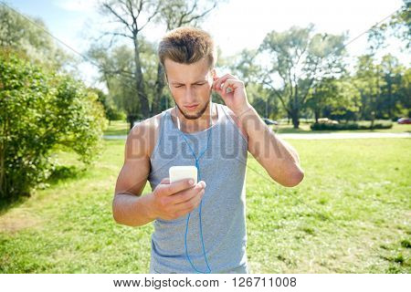 fitness, sport, technology and lifestyle concept - young man with smartphone and earphones listening to music at summer park