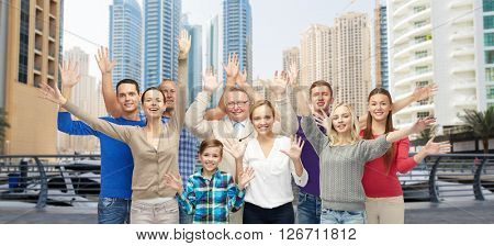 family, travel, tourism and people concept - group of smiling men, women and boy having fun and waving hands over dubai city street background