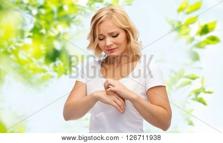 people, healthcare, dermatology, allergy and health problem concept - unhappy woman suffering from hand inch over green natural background
