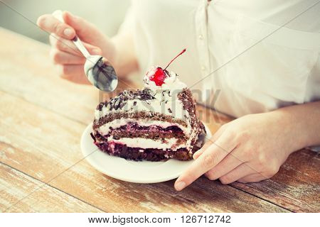 food, junk-food, culinary, baking and holidays concept - close up of woman eating chocolate cherry cake with spoon and sitting at wooden table