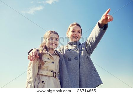 people, children, friends and friendship concept -happy little girls hugging and pointing finger outdoors