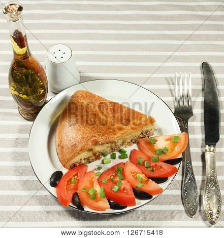 Serve the fish pie with slices of tomatoes green onions and olives on a white plate. Spices drenched with olive oil in bottle.