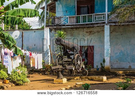 Hell Ville Madagascar - December 19 2015: Old cannon in the courtyard of an apartment house in the town of Hell Ville Nosy Be Island Madagascar. In 1904 - 1905 the Imperial Russian squadron stayed in Nosy Be for four months on the road to war with Japan.