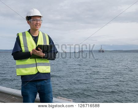 An asian engineer holding a clip board and standing in front of semi submersible oil rig