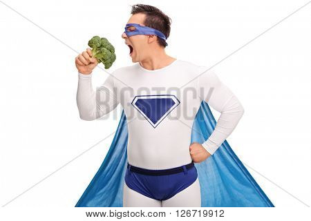 Young guy in a superhero outfit taking a bite of a large piece of broccoli isolated on white background