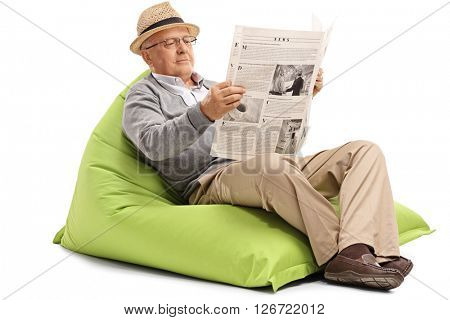 Relaxed mature man reading a newspaper seated on a green beanbag isolated on white background