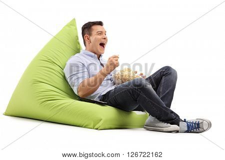 Young joyful guy eating popcorn and watching something seated on a green beanbag isolated on white background