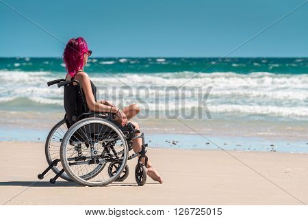 Disabled woman in the wheelchair at the beach enjoying the view