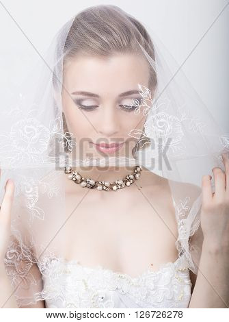 Beautiful bride with fashion wedding hairstyle. Close-up portrait of young gorgeous bride. Wedding. girl covers her face with a veil.