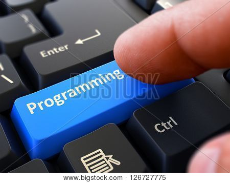 Computer User Presses Blue Button Programming on Black Keyboard. Closeup View. Blurred Background.