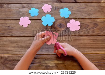 Child cuts a flower of paper. Child holds paper and scissors in his hands