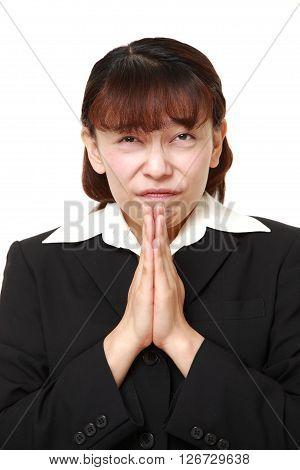 studio shot of businesswoman folding her hands in prayer