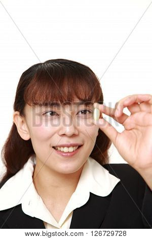 Asian businesswoman takes a supplement on white background