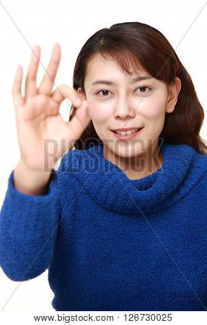 studio shot of Asian woman showing perfect sign on white background