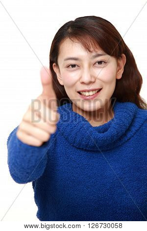 studio shot of Asian woman with thumbs up gesture on white background