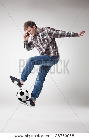 Portrait  of young man with smart phone and football ball on gray background. concept of continuous soccer practice