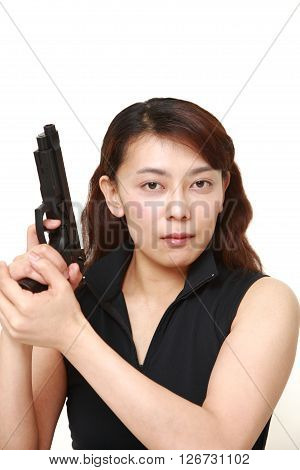 studio shot of woman with a handgun on white background
