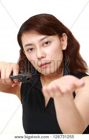 studio shot of female robber with a handgun