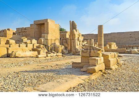 The massive stone sculpture of Egyptian Pharaoh among the ruins of Karnak Temple Luxor.