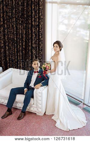 Young wedding couple enjoying romantic moments indoors sitting on sofa against window. Beautiful modern interior