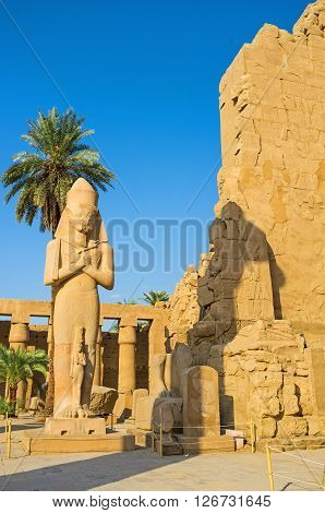 LUXOR EGYPT - OCTOBER 7 2014: The statue of Ramesses II with crossed arms holding crook and flail (symbols of kingship) with the small statue of Princess Bent-anta at his fit Great Court of Karnak Temple  on October 7 in Luxor.