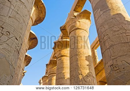 LUXOR EGYPT - OCTOBER 7 2014: The rows of the massive stone columns covered with the reliefs with ancient hieroglyphs pharaohs and gods in the Hypostyle Hall of Karnak Temple  on October 7 in Luxor.