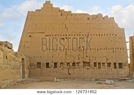The massive stone wall with the numerous longitudinal cracks is the preserved part of the Seventh Pylon of Karnak Temple Luxor Egypt.