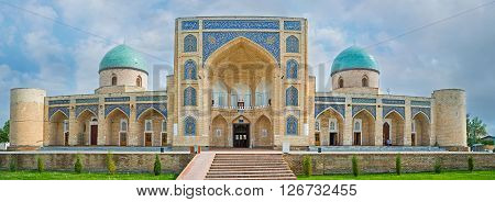 The facade of the Norbut-biy Madrasah with the huge portal decorated with arabesques and two domes covered with the glazed tiles Kokand Uzbekistan.
