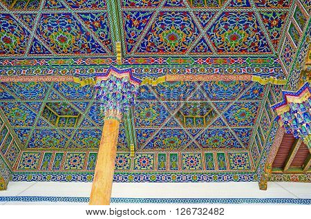 KOKAND UZBEKISTAN - MAY 6 2015: The ceiling of the Iwan in Jami Mosque covered with the islamic patterns and supported by the wooden pillars with the carved colorful capitals on May 6 in Kokand.