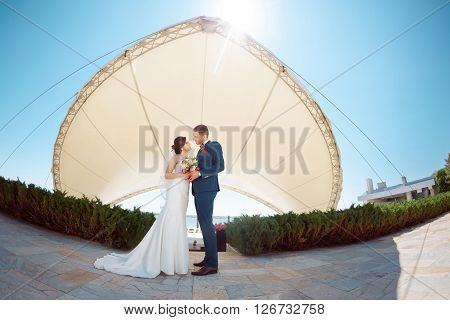 Young wedding couple looking to each other outside against modern buildings. Fisheye lens