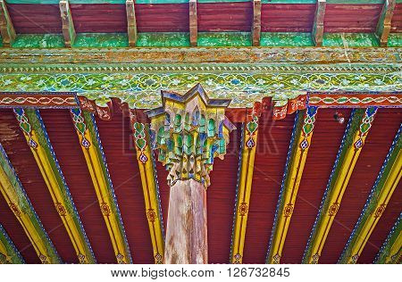 KOKAND UZBEKISTAN - MAY 6 2015: The carvings and painted ornaments are traditional decorative elements for the landmarks of Fergana Valley such as this ceiling and pillar in the Khudayar Khan Palace on May 6 in Kokand.