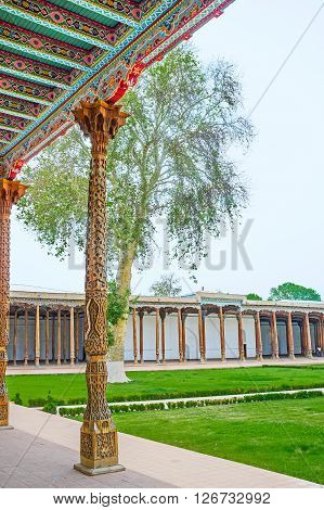 KOKAND UZBEKISTAN - MAY 6 2015: The Jami Mosque minaret seen through the rows of the wooden pillars of its Iwan on May 6 in Kokand.