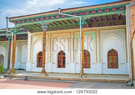KOKAND UZBEKISTAN - MAY 6 2015: The courtyard of Khudayar Khan Palace with the shady arcades decorated ceilings carved wooden pillars and ornaments on the plaster walls on May 6 in Kokand.