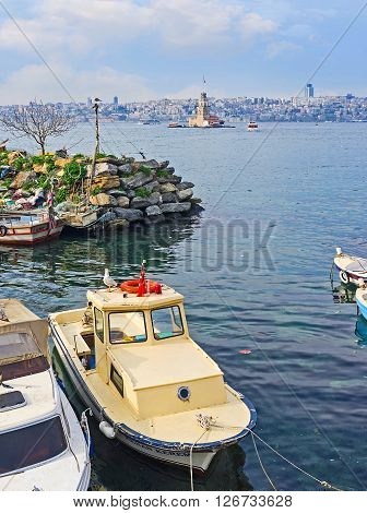 ISTANBUL TURKEY - JANUARY 21 2015: The small fishing boats in harbor and the medieval lighthouse on the background on January 21 in Istanbul.
