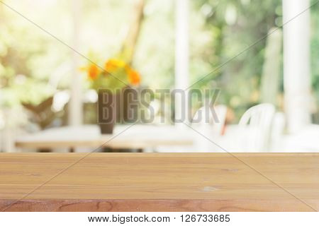 Wooden board empty table blurred background. Perspective brown wood over blur flower vase in coffee shop - can be used for display or montage your products.Mock up for display of product.
