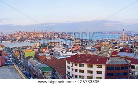 The old roofs of the Fatih district with the blue waters of Golden Horn Bay and Beyoglu district in the sunset rays on the background Istanbul Turkey.