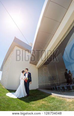 Young wedding couple enjoying romantic moments outside against modern buildings. Fisheye lens photo