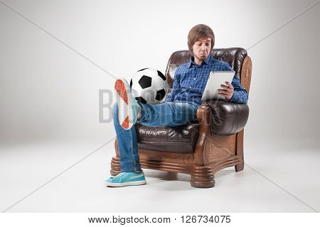 Portrait  of young man sitting with laptop and football ball on gray background. concept of continuous soccer practice