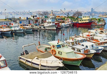 ISTANBUL TURKEY - JANUARY 21 2015: The old fishing boats in harbor in Uskudar district with the Maiden's Tower on the background on January 21 in Istanbul.
