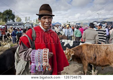 SAQUISILI, ECUADOR - MAY 18, 2014: Indian unidentified, selling handloom woven belts in the Andean market Saquisili­