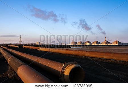 Nuclear energy and pollution. The huge plant on the background of lying pipes.