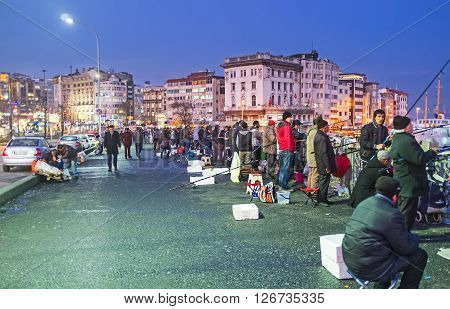 ISTANBUL TURKEY - JANUARY 21 2015: The local fishermen can stay on Galata Bridge till the dark night on January 21 in Istanbul.
