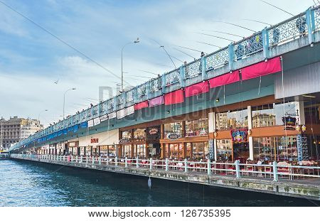 ISTANBUL TURKEY - JANUARY 21 2015: The Galata bridge offers different ways of time spending such as fishing on its top level or relax in cafe on the lower one on January 21 in Istanbul.