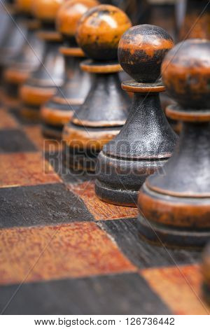 vintage wooden black pawns chess pieces in row focus on second piece