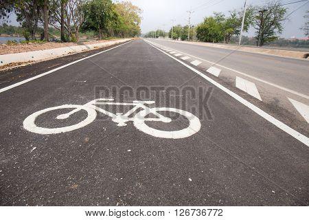 Closeup bicycle lane sign on black road